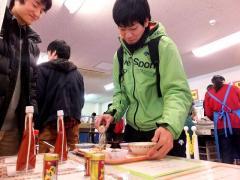 唐辛子調味料をかける学生