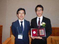 受賞した黄宸佑さん(右)と指導教員の竹田准教授(左)