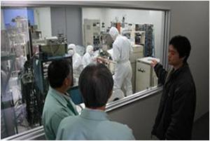 クリーンルーム内で高性能RF薄膜デバイスや光プローブ電流センサ用磁性薄膜をスパッタ装置で成膜する学生と、企業の方にその工程を説明する曽根原准教授