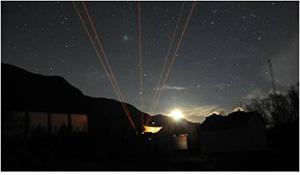 夜空に向けて射出される黄色のレーザー。オーロラ活動時の大気温度の空間変動を調べるため、5方向に射出