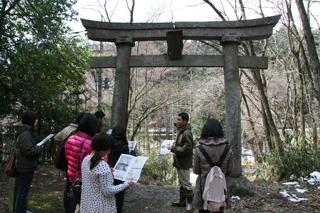 鳥居の下で話を聞く学生たち