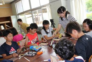 子供たちにメカフィッシュの作り方を指導するバイオメカニクス研究室の学生