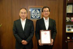 認証書を手にする濱田学長(右)と<br/>佐々木長野県中信労政事務所長(左)
